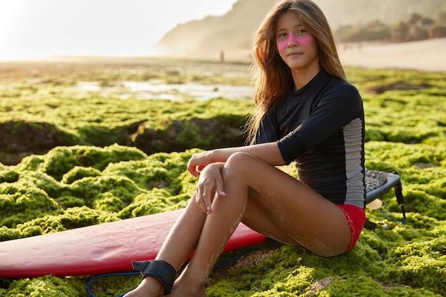 Zdjęcie pięknej długowłosej surfera w stroju kąpielowym