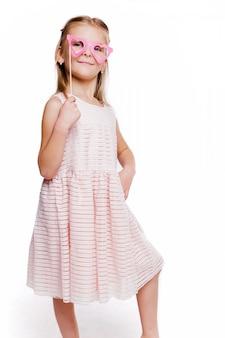 Zdjęcie pięknej dziewczyny w różowej sukience i okularach wykonane z tektury w kształcie serduszka