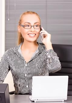 Zdjęcie pięknej dziewczyny z telefonem komórkowym w biurze