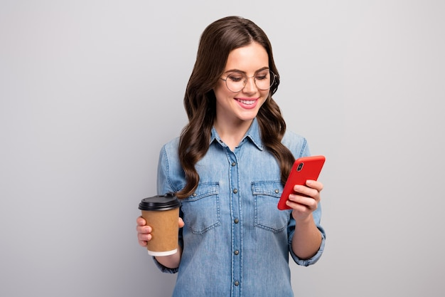 Zdjęcie pięknej freelancer pani trzymaj kubek papierowy gorąca kawa napój przerwa w pracy przeglądanie telefonu czytaj post nosić specyfikacje na co dzień dżinsy koszula dżinsowa na białym tle szary kolor