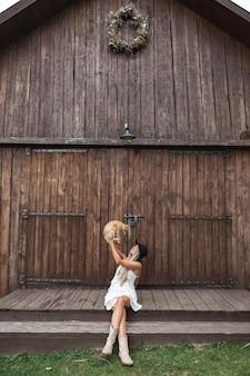 Zdjęcie pięknej i seksownej blond kobiety w wiosce, siedzącej na schodach przed drewnianą stodołą
