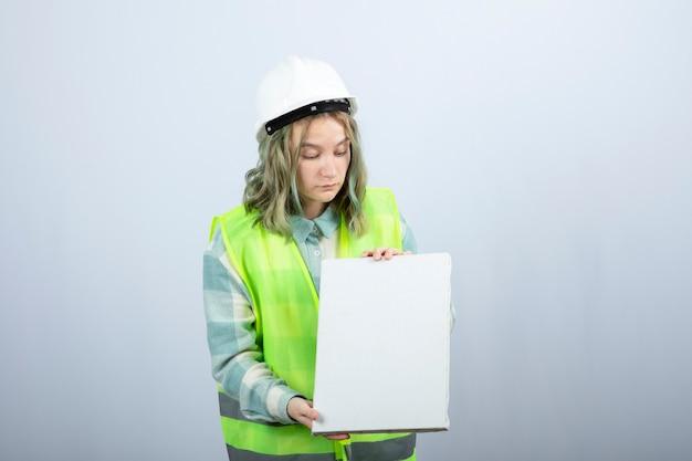 Zdjęcie pięknej inżynier kobieta trzymając puste płótno na białej ścianie. wysokiej jakości zdjęcie