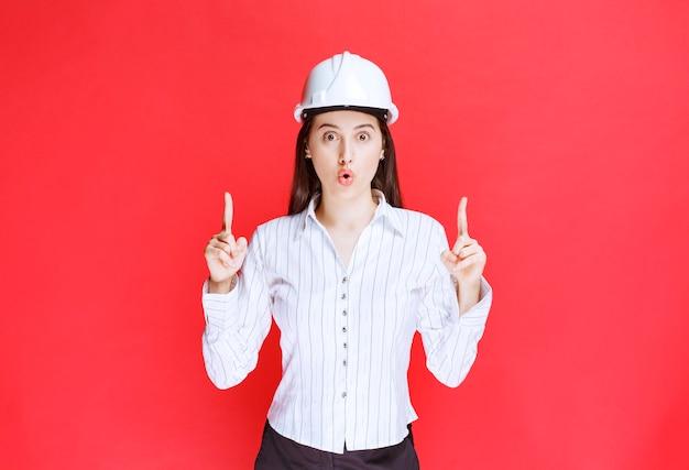 Zdjęcie pięknej kobiety biznesu w kapeluszu bezpieczeństwa, wskazując palcami.