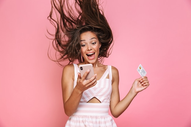 Zdjęcie pięknej kobiety lat 20. na sobie sukienkę, uśmiechając się i trzymając telefon komórkowy z drżeniem włosów, na białym tle nad różową ścianą