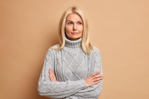 Zdjęcie pięknej kobiety w średnim wieku o blond włosach, z założonymi rękoma, myśli o czymś, co zastanawia się nad planami na przyszłość, nosi ciepły sweter.