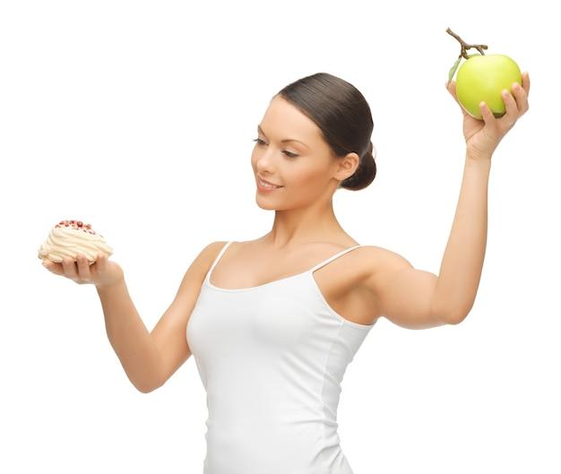 Zdjęcie pięknej kobiety z ciastem i jabłkiem