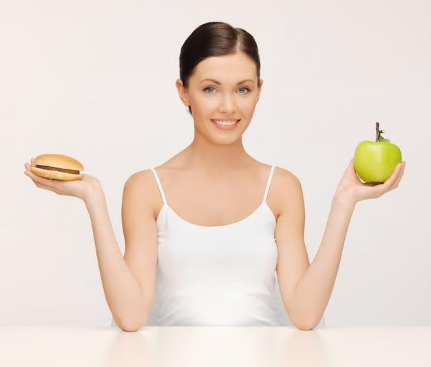 Zdjęcie pięknej kobiety z hamburgerem i jabłkiem