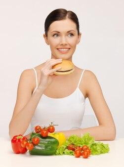 Zdjęcie pięknej kobiety z hamburgerem i warzywami