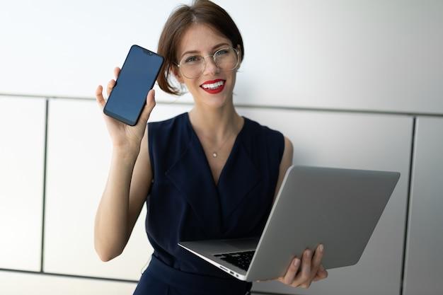 Zdjęcie pięknej kobiety z krótkimi ciemnymi włosami w garniturze umówił się na spotkanie i czeka na koleżankę w pobliżu biura.