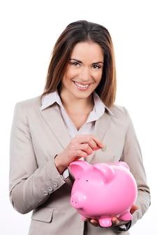 Zdjęcie pięknej kobiety z piggy bank i pieniądze