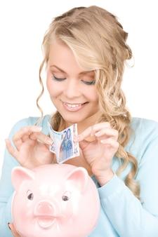 Zdjęcie pięknej kobiety z skarbonką i pieniędzmi