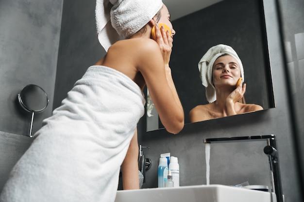Zdjęcie pięknej kobiety zawiniętej w ręcznik myjącą twarz gąbką