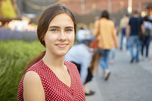 Zdjęcie pięknej, ładnej dwudziestokilkuletniej dziewczyny budzącej się na świeżym powietrzu na tętniącej życiem ulicy, cieszącej się miłym letnim dniem i radośnie uśmiechającej się. koncepcja ludzie, lato, młodzież, podróże i styl życia