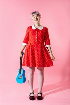 Zdjęcie pięknej laleczki z krótkimi jasnofioletowymi włosami na sobie czerwoną sukienkę z niebieskim ukulele na różowej ścianie