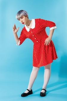 Zdjęcie pięknej lalki z krótkimi jasnofioletowymi włosami na sobie czerwoną sukienkę na niebieskiej ścianie