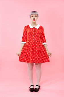 Zdjęcie pięknej lalki z krótkimi jasnofioletowymi włosami na sobie czerwoną sukienkę na różowej ścianie