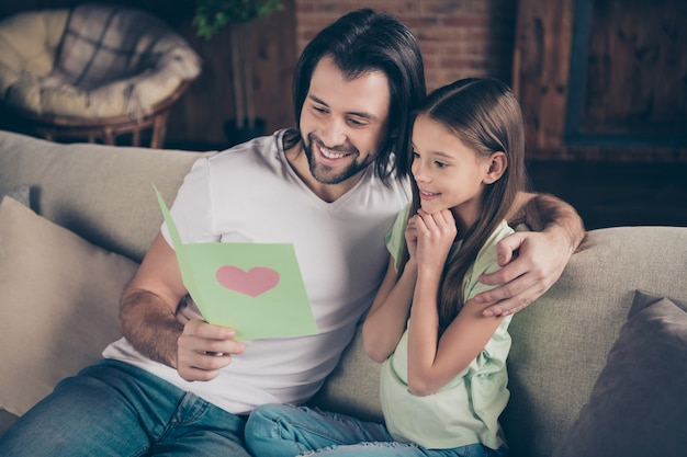 Zdjęcie pięknej małej uroczej dziewczynki i przystojnego młodego taty siedzą na wygodnej kanapie