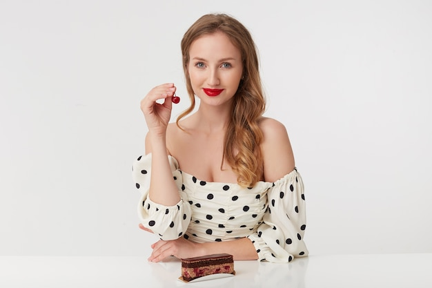Zdjęcie pięknej młodej blondynki z czerwonymi ustami w sukience w kropki. siedzenie przy stole z ciastem, trzymanie w dłoniach wiśni. uśmiechnięty na białym tle nad białym tle.