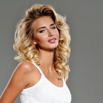 Zdjęcie pięknej młodej dziewczyny blond z kręconymi włosami. zbliżenie atrakcyjna zmysłowa twarz białej kobiety z długimi włosami. makijaż smokey eye.