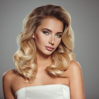 Zdjęcie pięknej młodej kobiety blond z kręconymi włosami. zbliżenie atrakcyjna zmysłowa twarz białej kobiety. makijaż smokey eye.