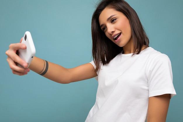 Zdjęcie pięknej młodej kobiety brunetka ubrana na co dzień biały t-shirt