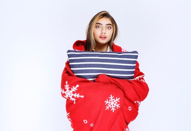 Zdjęcie pięknej młodej kobiety owiniętej w miękki koc i trzymającej poduszkę.