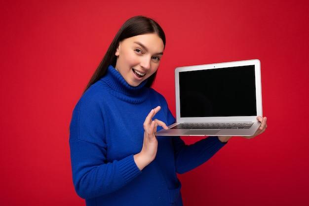 Zdjęcie pięknej młodej kobiety posiadania komputera przenośnego patrząc na kamery na białym tle nad kolorowym tłem.
