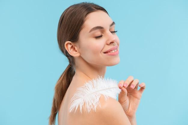 Zdjęcie pięknej młodej kobiety pozowanie na białym tle trzymając pióro.