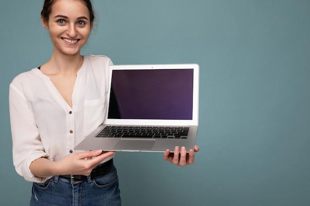 Zdjęcie pięknej młodej kobiety trzymającej komputer laptop patrząc na kamery na białym tle nad kolorowym tłem.