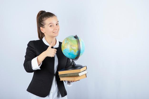 Zdjęcie pięknej młodej nauczycielki z książkami i kulą ziemską, dając kciuki do góry na białym tle.