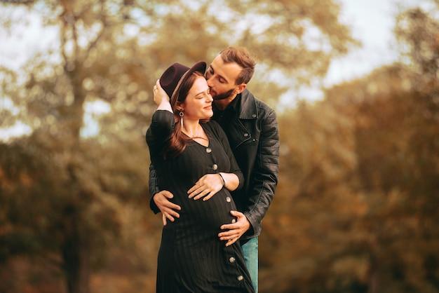 Zdjęcie pięknej młodej rodziny z kobietą w ciąży w parku