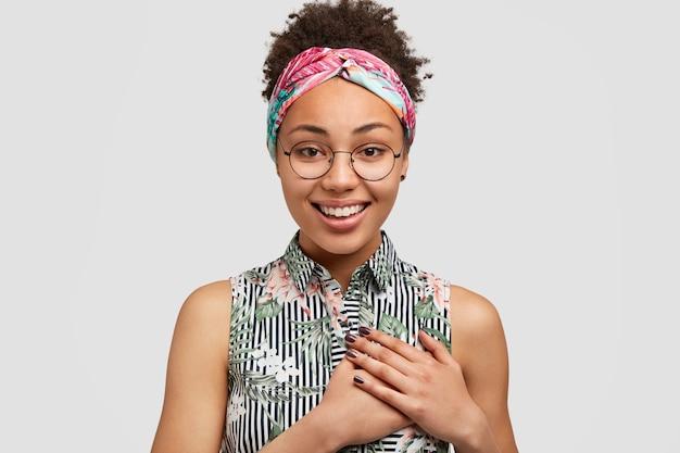 Zdjęcie pięknej młodej suczki o ciemnej karnacji, trzymającej dłonie na sercu, uśmiechającej się pozytywnie, wzruszonej komplementem otrzymanym od chłopaka, stoi pod białą ścianą. optymistyczna dziewczyna