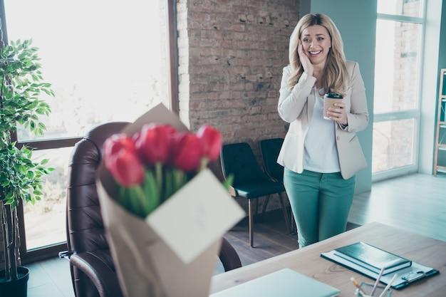 Zdjęcie pięknej pani biznesu przyszedł zaskoczony bukietem niespodzianką