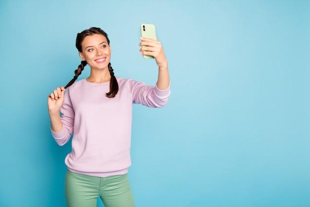Zdjęcie pięknej pani trzymającej telefon ręka robiąc śmieszne selfie tłumaczenie bloga online rozmowa wideo nosić dorywczo różowy sweter zielone spodnie na białym tle niebieski kolor