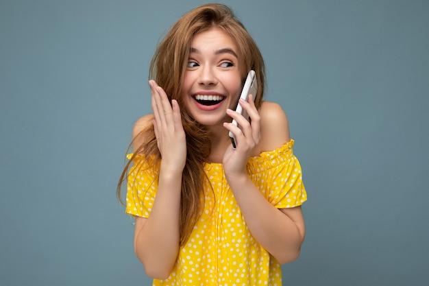 Zdjęcie pięknej pozytywnej zaskoczonej młodej blondynki na sobie stylową żółtą letnią sukienkę
