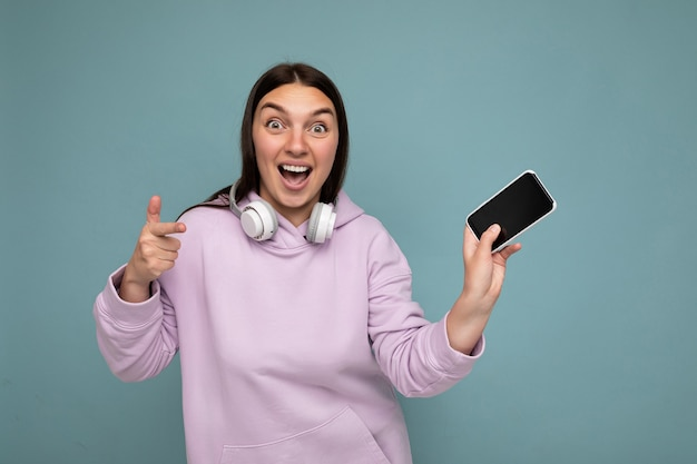 Zdjęcie pięknej pozytywnej zdumionej młodej brunetki noszącej fioletową bluzę z kapturem odizolowaną na niebiesko