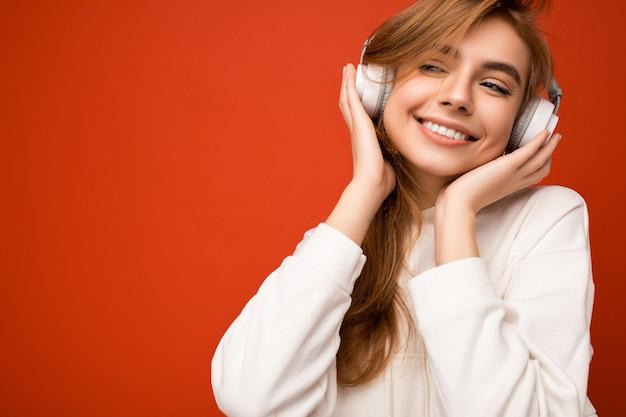 Zdjęcie pięknej seksownej szczęśliwej uśmiechniętej młodej blondynki na sobie białą bluzę z kapturem na białym tle na kolorowe