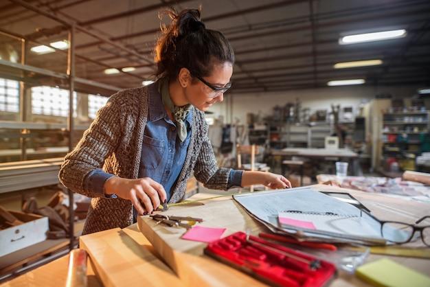 Zdjęcie pięknej, skoncentrowanej kobiety w średnim wieku, architekta w jej warsztacie pracującym nad nowymi projektami
