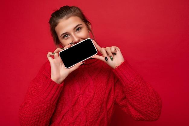 Zdjęcie pięknej ślicznej młodej kobiety ubrane w ciepły czerwony sweter na białym tle na czerwonym tle ściany trzymając smartfon i pokazując telefon z pustym wyświetlaczem do makiety patrząc na kamery.