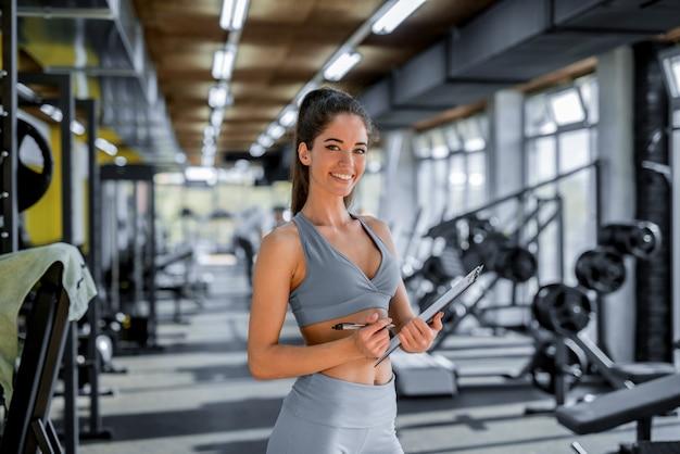 Zdjęcie pięknej sportowej żeńskiej osobistej trener fitness pozowanie przed kamerą w jasnej siłowni.