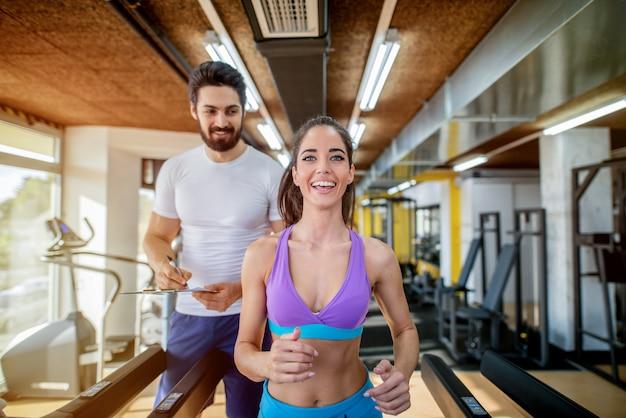 Zdjęcie pięknej sprawnej kobiety na bieżni w siłowni, podczas gdy jej osobisty trener fitness stoi za nią.
