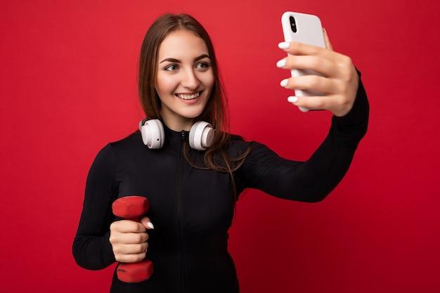 Zdjęcie pięknej szczęśliwej młodej brunetki noszącej czarne sportowe ubrania białe słuchawki nad