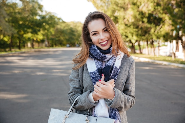 Zdjęcie pięknej szczęśliwej pani sobie szalik uśmiechający się na tle przyrody i trzymając torbę.