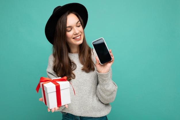 Zdjęcie pięknej szczęśliwej radosnej młodej brunet kobiety na białym tle na niebieskim tle ściany ubrana na czarno