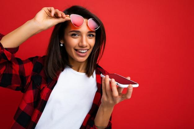 Zdjęcie pięknej szczęśliwej radosnej młodej brunet kobiety na sobie stylową czerwoną koszulę białą koszulkę i czerwone okulary przeciwsłoneczne