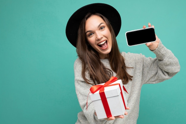 Zdjęcie pięknej szczęśliwej radosnej młodej kobiety brunetka samodzielnie na niebieskim tle ściany sobie
