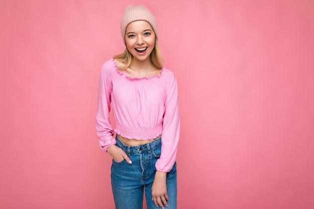 Zdjęcie pięknej, szczęśliwej uśmiechniętej, radosnej młodej blondynki, odizolowanej na różowej ścianie w tle