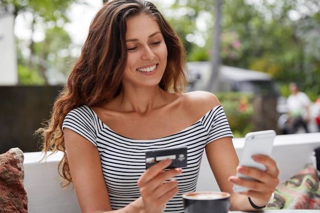 Zdjęcie pięknej turystki używa nowoczesnego telefonu i karty kredytowej do rezerwacji biletów online
