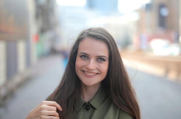 Zdjęcie pięknej uśmiechniętej kobiety z hipnotyzującymi zielonymi oczami na rozmytym tle