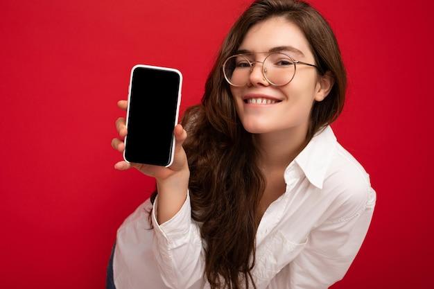 Zdjęcie pięknej uśmiechniętej młodej kobiety, dobrze wyglądającej, noszącej dorywczo stylowy strój stojący na białym tle